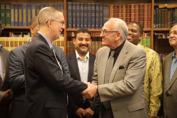 General Overseer Sam Clements and Dr. John Wagenvald shake hands at the conclusion of the signing.
